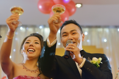 bridal: Natural candid Asian Chinese wedding dinner reception, bride and groom champagne toasting. Stock Photo