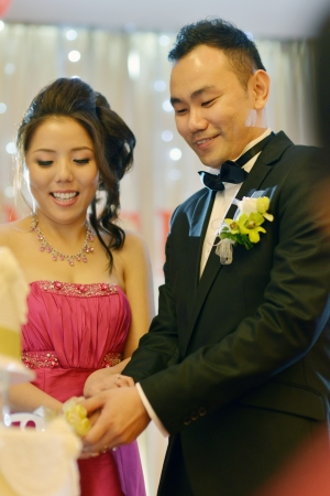 Bride and groom cake cutting, natural candid. Asian Chinese wedding dinner reception. photo
