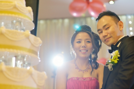 Asian Chinese wedding dinner reception. Bride and groom cake cutting.
