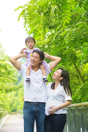 Happy Asian family outdoor. Father piggyback his daughter walking in garden park with pregnant wife. Healthy lifestyle.  photo