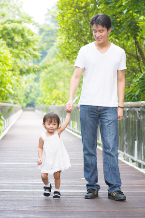 Happy Asian family outdoor activity. Father and daughter holding hands walking on garden path. photo