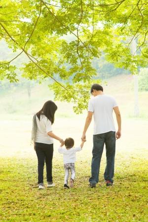 familias unidas: Actividad al aire libre de la familia asiática feliz. Vista posterior de los padres y la hija que se divierten y caminar en el césped verde. Foto de archivo