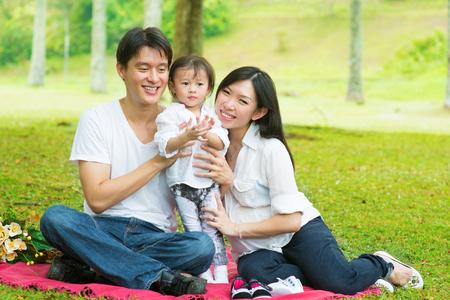 asia family: Actividad al aire libre de la familia asi�tica feliz. Los padres y la hija de tener, picnic en el jard�n de c�sped verde. Foto de archivo