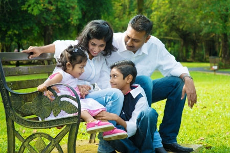 indian summer seasons: Happy Indian family at outdoor park. Candid portrait of parents and children having fun at garden park.