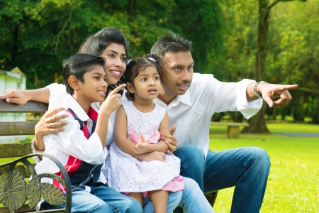 indian summer seasons: Happy Indian family at outdoor park. Candid portrait of parents and children having fun at garden park. Fingers pointing away.