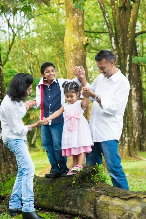 Happy Indian family at outdoor. Candid portrait of parents and children having fun at garden park. Exploring nature, leisure lifestyle.