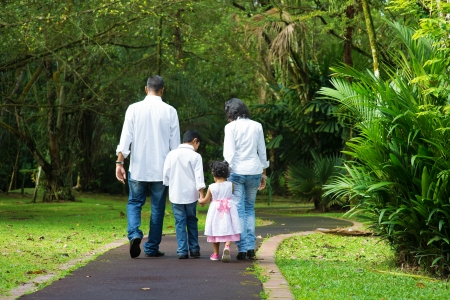 Indian family at outdoor. Rear view of parents and children walking on garden path. Exploring nature, leisure lifestyle.