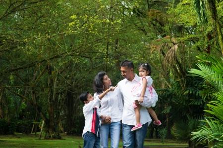 indianen: Indische familie op buiten. Ouders en kinderen lopen op tuinpad. Verkennen van de natuur, vrije tijd levensstijl.