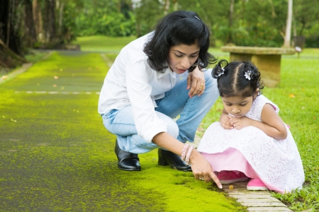 Indian family outdoor activity. Candid portrait of mother and daughter exploring on nature, outdoors education. Stock Photo