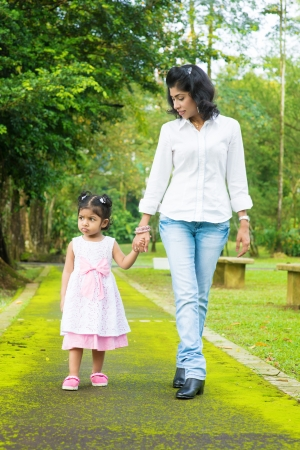 Indian family walking on garden path. Mother and daughter holding hands at outdoor park.