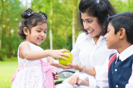 indianen: Gelukkige Indische familie. Aziatisch meisje het delen van een groene appel op outdoor met moeder en broer of zus. Stockfoto