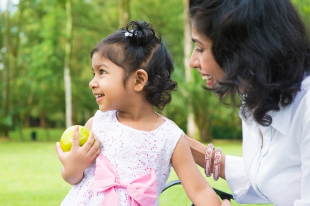 Happy Indian family. Asian girl holding an green apple at outdoor with mother. photo
