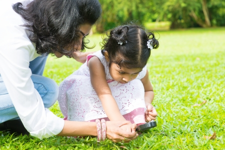 Cute Indian girl peeking through magnifying glass with parent on green lawn. Mother and daughter exploring nature at outdoor garden. photo