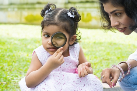Daughter at outdoor green park with mother. Cute Indian girl peeking through magnifying glass with parent. photo