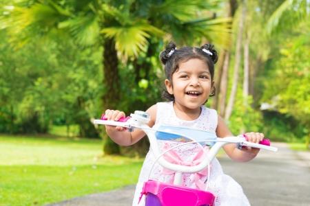 Cute Indian girl biking at outdoor garden. Child having fun with bicycle.