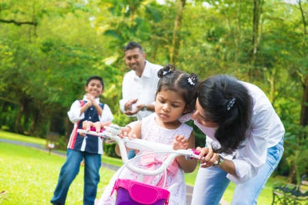 father teaching daughter: Indian family outdoor activity. Asian mother teaching little girl to ride a bike at the park in the morning. Stock Photo
