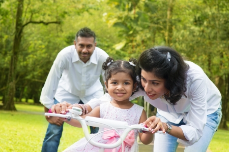 indian happy family: Indian family outdoor activity. Asian parent teaching child to ride a bike at the park in the morning. Stock Photo