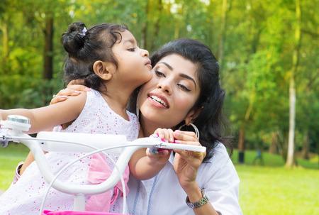 indianen: Indische familie outdoor activiteit. Aziatische Moeder onderwijs dochter fietsen in het park in de ochtend. Kind zoenen ouder.