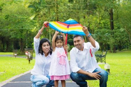 papalote: Familia india divertida actividad al aire libre. Padre y madre que vuela una cometa de colores con la hija.
