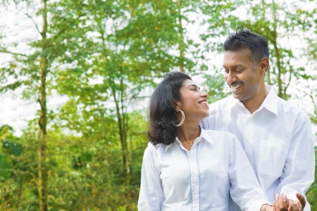 edad media: Pareja de indios en parque verde. Retrato de mediados de la edad hermosa familia indio en traje moderno de pie al aire libre. Marido indio y modelo de esposa. Foto de archivo