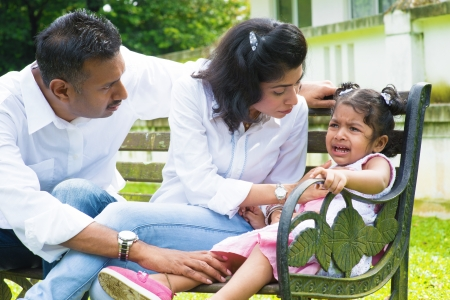 parent and child: Indian family outdoor. Parents is comforting their crying daughter.