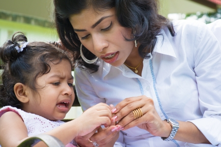 Indian family outdoor. Mother is comforting her crying daughter with injured finger. photo