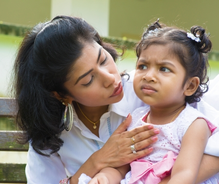 tiredness: Indian family outdoor. Modern mother is comforting her crying daughter.