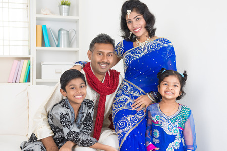 Portrait of happy Indian family at home. Living lifestyle of parents and children in their traditional dress in modern house.
