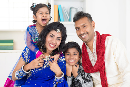 Happy smiling Indian family at home. Living lifestyle of parents and children in their traditional dress in modern house. photo