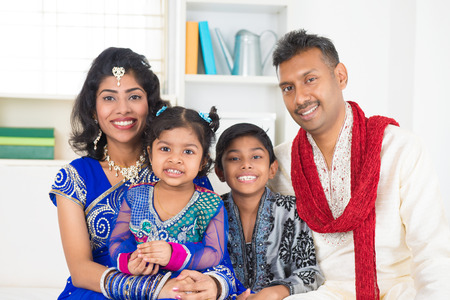 Happy Indian family at home. Living lifestyle of parents and children in their traditional dress in modern house.