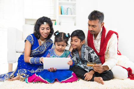 Indian Asian family using tablet pc computer online shopping with credit card at home. India family living lifestyle. Happy smiling parents and children. photo