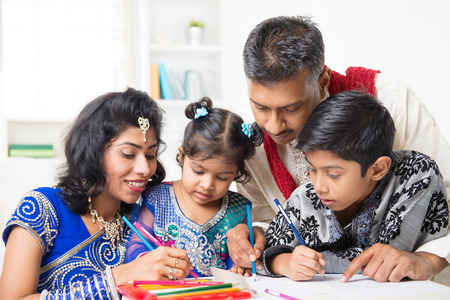 Asian Indian family drawing and painting picture at home. India family lifestyle. Happy parents and children having fun. photo