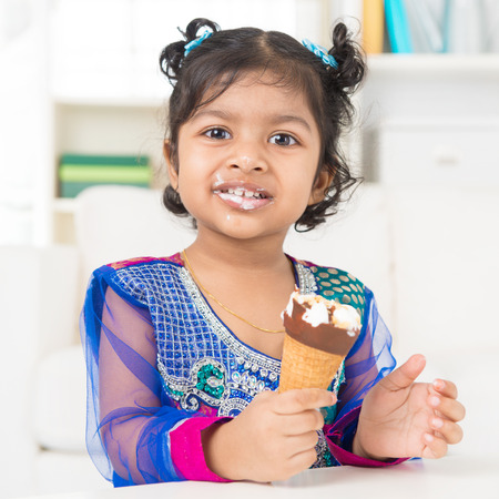 Eating ice cream. Cute Indian Asian girl enjoying an ice cream. Beautiful child model at home.