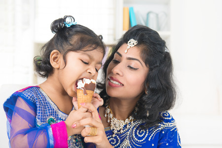 Eating ice-cream. Happy Asian India family sharing ice-cream at home. Beautiful Indian child licking ice-cream cone. photo