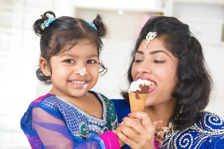 Eating ice-cream. Happy Asian India family sharing ice-cream at home. Beautiful Indian child feeding mother. photo