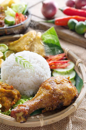 lunch meal: Popular delicious Indonesian local food nasi ayam penyet, indonesian fried chicken rice with sambal belacan. Fresh hot with steam smoke.