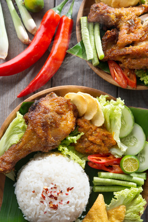 Popular Indonesian local food nasi ayam penyet, indonesian fried chicken rice. Fresh hot with steam smoke. photo