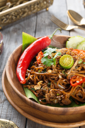 goreng: Mee goreng mamak or mi goreng, Indonesian and Malaysian cuisine, spicy fried noodles with wooden dining table setting. Fresh hot with steamed smoke.