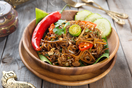 goreng: Mi goreng or mee goreng mamak, Indonesian and Malaysian cuisine, spicy fried noodles with wooden dining table setting. Fresh hot with steamed smoke.