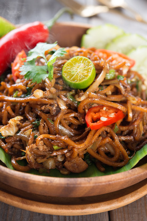 chinese noodle: Indonesian and Malaysian cuisine, mi goreng or mee goreng mamak,  spicy fried noodles with wooden dining table setting. Fresh hot with steamed smoke.