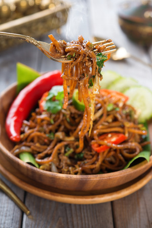 Indonesian and Malaysian cuisine, spicy fried noodles, mi goreng or mee goreng mamak with wooden dining table setting. Fresh hot with steamed smoke. photo