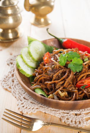 Spicy fried noodles. Indonesian and Malaysian cuisine, mi goreng or mee goreng mamak with wooden dining table setting. Fresh hot with steamed smoke. photo