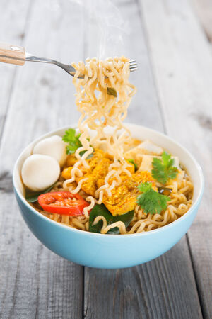 Spicy curry instant noodles holding with fork. Asian cuisine, ready to serve on wooden dining table setting. Fresh hot with steamed smoke.