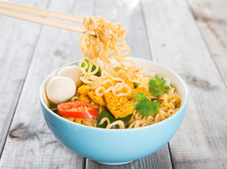 instant noodle: Spicy curry instant noodles with chopsticks. Asian cuisine, ready to serve on wooden dining table setting. Fresh hot with steamed smoke.