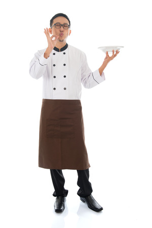 Full body Asian chef holding an empty plate, showing tasty and satisfied hand sign, standing isolated on white background. photo