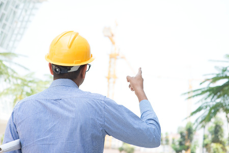 indian male: Rear view of Indian male site contractor engineer with hard hat pointing to a construction site. Stock Photo