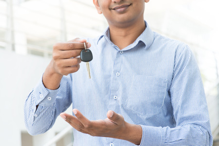 Young Asian Indian estate agent or salesman holding a key photo