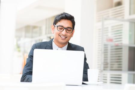 ufficio aziendale: Giovane imprenditore indiano asiatici utilizzando un computer notebook o laptop durante la pausa di ufficio al caff�, rilassante con una tazza di caff� Archivio Fotografico