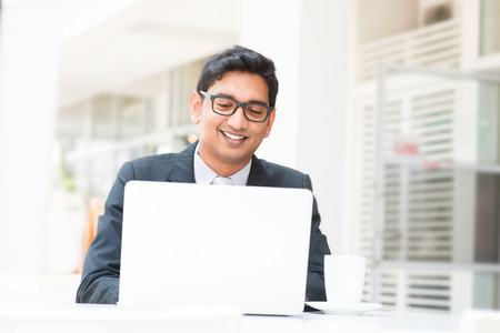 people at work: Young Asian Indian businessman using a notebook computer or laptop during office break at cafe, relaxing with a cup of coffee Stock Photo