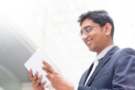 Candid young Asian Indian businessman using digital tablet pc at outdoor building photo